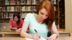 Female university student redhead writing in the library Stock Footage