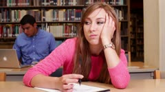 Female university student trying to write in the library - stock footage