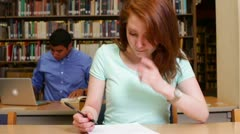 Female redhead university student studying in the library - stock footage