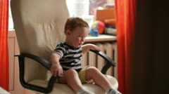 Two year old boy is spinning on chair. Stock Footage