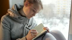 Young girl writing in her journal while sitting at a large window. Stock Footage