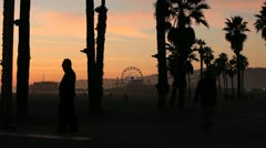 Boardwalk Silhouettes in front of Santa Monica Pier - stock footage