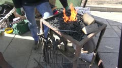 Blacksmith in agriculture fair  forging metal object Stock Footage
