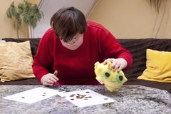 Disabled woman looking desperately for little money Stock Photos