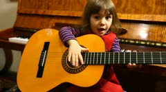 Little Baby Girl Plays Guitar Stock Footage