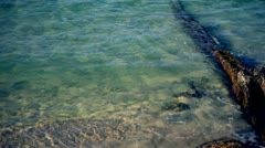 Clear water on a beach and barrier wall Stock Footage