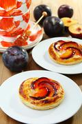 Puff pastry with cream  and plums. Stock Photos