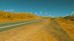 Cars pass Wind Farm in California Stock Footage