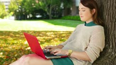 Female university college student studying outside under a tree Stock Footage