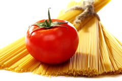 spaghetti in a bunch and ripe tomato on a white background. - stock photo