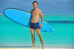 man with surf board on beach - stock photo