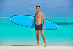 Stock Photo of man with surf board on beach