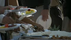 People serving themselves at a catered Hawaiian Luau Stock Footage