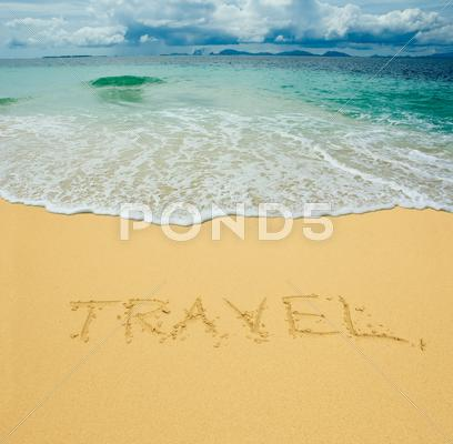 Stock photo of travel written in a sandy tropical beach