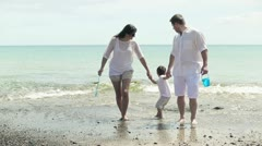 Happy family in white clothes running on the beach Stock Footage