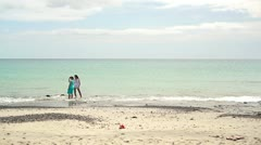 Two women standing on the beach in the distance Stock Footage