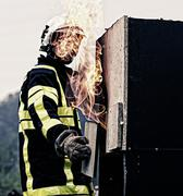 Fireman covering a flame - stock photo