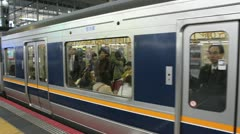 KYOTO - MARCH 2013: A subway car full of passengers departs from a Kyoto station Stock Footage