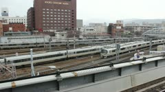 Commuter trains pass by Kyoto Station in Kyoto, Japan circa March 2013. - stock footage
