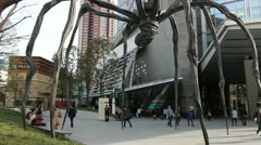 TOKYO - CIRCA MARCH 2013: People pass under Louise Bourgeois spider sculpture in Stock Footage