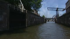 Amsterdam canal district vehicle shot through open lock sluice in canal Stock Footage