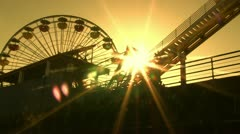 Silhouette of amusement park rides with Sun Stock Footage
