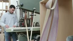 Woodworker sawing wood with a band saw - carpenter in carpentery - dolly Stock Footage