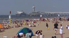 North Sea Beach at Scheveningen, People sunbath with pier in background Stock Footage