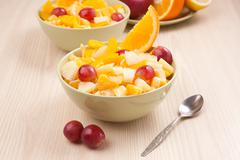 Stock Photo of two bowls with fruit salad on wooden table with spoon