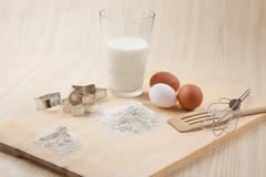 glass of milk, whisk, cookie cutter forms and eggs on wooden table - stock photo