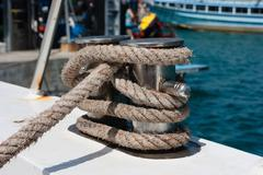 knot on a bollard of a boat. blue sea in a background. - stock photo