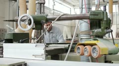Woodworker (carpenter) in the factory use a industrial planer - dolly Stock Footage