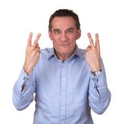 Attractive frustrated man in blue shirt giving finger sign Stock Photos