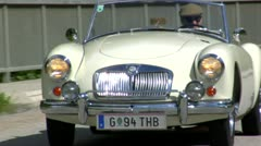Vintage Classic Car Convertible Jaguar Driving through European roadside Stock Footage