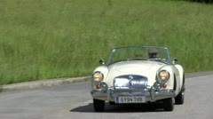 Classic Jaguar car travels along the curve of the road Stock Footage