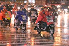 People riding scooters in Shanghai by rainy day - stock photo