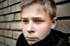Upset boy leaning against a wall Stock Photos