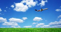 Airplane over grassy field Stock Photos