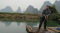 Guilin China Chinese man pushing bamboo raft with pole on river Stock Footage