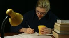 Woman in bathrobe writing at night Stock Footage