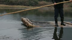 Guilin China Chinese man pushing bamboo raft with pole on river - stock footage