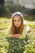 a pretty young girl lying on the grass amongst flowers. - stock photo