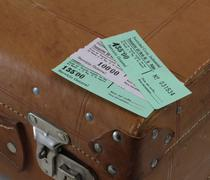 admission tickets on a suitcase - stock photo