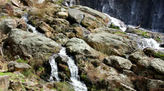 Water flows over rocks by a dam Stock Footage