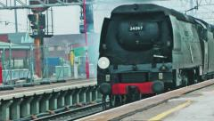 Vintage steam train passing through a station Stock Footage