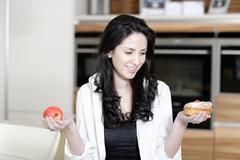 Stock Photo of woman choosing cake or fruit