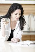 Woman reading recipe book Stock Photos