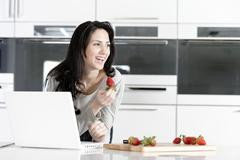 woman in kitchen reading recipe - stock photo