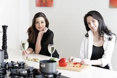 two friends in a kitchen cooking - stock photo