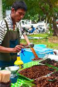 phuket, thailand - march 01: thai man selling fried insects at market - stock photo